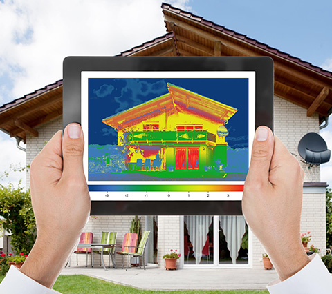 Image of Man Looking at Temperature Readings in Front of House